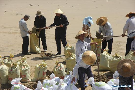 Staff workers reinforce dikes and dams with sand bags at a scenic spot in Wenling City, east China's Zhejiang Province, July 10, 2018. China Meteorological Administration on Tuesday issued this year's first red alert for typhoon as the Typhoon Maria or the 8th of the year approaches the Chinese coast. Typhoon Maria is likely to sweep Taiwan, Fujian, Jiangxi and part of Zhejiang on Tuesday and Wednesday. (Xinhua/Jin Yunguo)