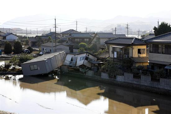 Photo taken on July 10, 2018, shows submerged and destroyed houses in a flooded area in Kurashiki, Okayama Prefecture, Japan. The death toll in the wake of torrential rainfall causing flooding and landslides in western Japan reached 148 people, officials said Tuesday. (Xinhua/Ma Ping)