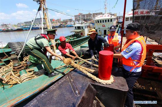 Police officers and soldiers help fishermen moor fishing boats in Taizhou, east China's Zhejiang Province, July 10, 2018. China Meteorological Administration on Tuesday issued this year's first red alert for typhoon as the Typhoon Maria or the 8th of the year approaches the Chinese coast. Typhoon Maria is likely to sweep Taiwan, Fujian, Jiangxi and part of Zhejiang on Tuesday and Wednesday. (Xinhua/Jiang Youqin)