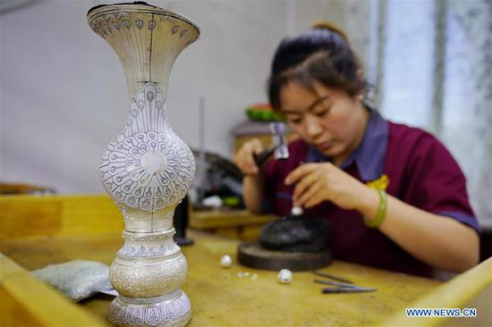 A worker makes a silverware at a workshop in Malanyu Township in Zunhua City, north China's Hebei Province, July 11, 2018. Gold and silver processing in Malanyu Township has a long history and the industry is expanding as craftsmen blend modern elements with traditional techniques in recent years. To date, there are more than 80 enterprises that provide over 2,000 jobs for local residents. (Xinhua/Mu Yu)