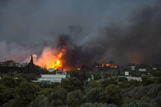 Flames rise as a wildfire burns in the town of Rafina, near Athens (Picture: Getty)