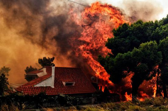 A house is threatened by a huge blaze during a wildfire in Kineta, near Athens, on Monday