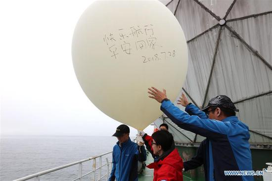 Researchers on China's research icebreaker Xuelong release a sounding balloon for meteorological observation on Bering Sea, during China's 9th Arctic expedition on July 28, 2018. (Xinhua/Shen Cheng)