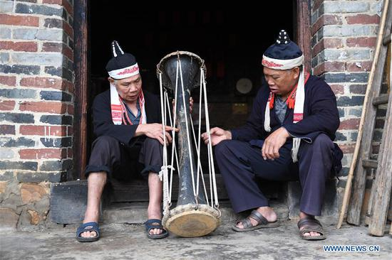 Villagers Pan Zhensong (L) and Pan Zhiming talk about making Huangni drums in Jinxiu Yao Autonomous County, south China's Guangxi Zhuang Autonomous Region, Aug. 1, 2018. The local Huangni drum dance was listed as one of the national intangible cultural heritage in 2011. (Xinhua/Lu Boan)