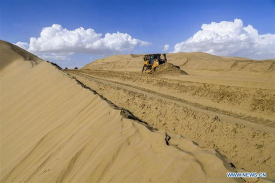 Photo taken on July 5, 2018 shows the construction site of the desert road linking Yuli County to Qiemo County in northwest China's Xinjiang Uygur Autonomous Region. As an important link of the Silk Road Economic Belt, Xinjiang is speeding up the development of transportation and logistics to connect east and west. By the end of 2017, the total length of roads in Xinjiang reached 186,000 km, with 4,578 km of expressways. (Xinhua/Hu Huhu)