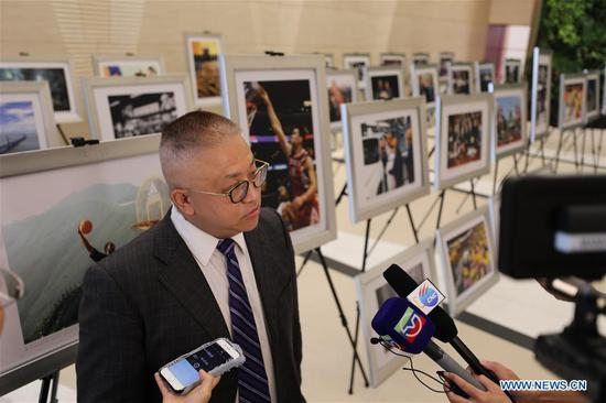 Huang Xiaojun, Executive Vice President of New York Branch, Bank of China, is interviewed at the photo exhibition