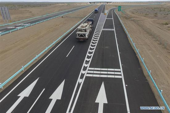Photo taken on July 15, 2017 shows trucks running on the Beijing-Urumqi Expressway in Hami, northwest China's Xinjiang Uygur Autonomous Region. As an important link of the Silk Road Economic Belt, Xinjiang is speeding up the development of transportation and logistics to connect east and west. By the end of 2017, the total length of roads in Xinjiang reached 186,000 km, with 4,578 km of expressways. (Xinhua/Cai Zengle)