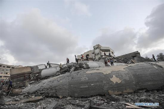 Palestinians search in the rubble of a building following an Israeli airstrike in Gaza City, on Aug. 9, 2018. The Israeli war jets launched 12 successive airstrikes on a building in west Gaza in response to rockets firing from Gaza into Israel, eyewitnesses and security sources said. Sources in western Gaza city said at least 18 civilians were injured in the new round of airstrikes carried out by Israel Thursday afternoon. (Xinhua/Wissam Nassar)