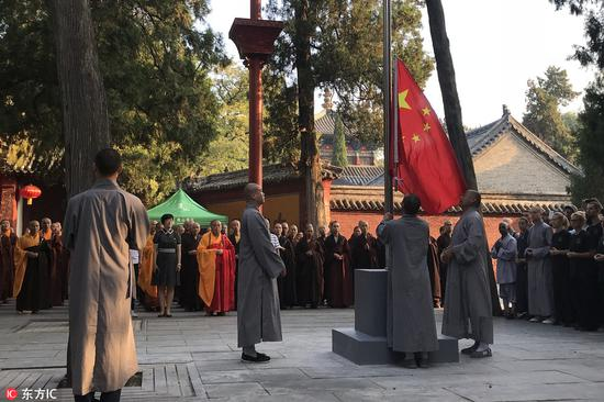 Monks raise the national flag during the flag-raising ceremony in Shaolin temple on Songshan mountain in Central China's Henan province on Aug 27, 2018. The flag-raising ceremony, the first in the temple in more than 1,500 years, helps the religious circles and believers to enhance national and civic consciousness and consolidate the sense of the Chinese nation community, according to sources from the temple. Foreign believers were also present to witness the ceremony. [Photo/IC]