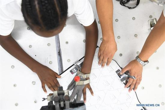 An Ethiopian worker of ANTEX Fashion Group learns cutting skill at a plant in Huzhou, east China's Zhejiang Province, Aug. 30, 2018. In 2017, Zhejiang's ANTEX Fashion Group set a branch in Ethiopia. To build a better team, the Ethiopian branch has sent 93 Ethiopian workers to China for six-month training. Besides learning production skills, these workers also learnt Chinese language, calligraphy and martial art in spare time.