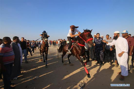 Palestinian men ride their horses as they compete in a local horse race in the southern Gaza Strip city of Rafah, on Sept. 9, 2018. (Xinhua/Khaled Omar)