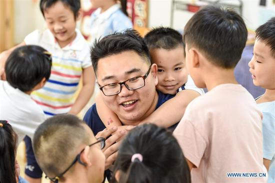 Guo Xinwang has fun with children at the Xiaoxihu kindergarten in Nanjing, capital of east China's Jiangsu Province, Sept. 4, 2018. Guo, born in 1993 and graduated from the Jiangsu Normal University, became the first and only male teacher of the Xiaoxihu kindergarten three years ago. There are 400 plus male teachers in Nanjing nowadays, up to three percent of the whole teachers working in kindergartens. (Xinhua/Li Bo)