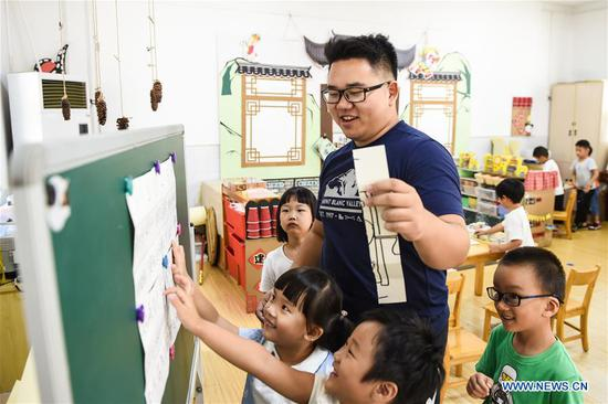 Guo Xinwang tells story for children at the Xiaoxihu kindergarten in Nanjing, capital of east China's Jiangsu Province, Sept. 6, 2018. Guo, born in 1993 and graduated from the Jiangsu Normal University, became the first and only male teacher of the Xiaoxihu kindergarten three years ago. There are 400 plus male teachers in Nanjing nowadays, up to three percent of the whole teachers working in kindergartens. (Xinhua/Li Bo)
