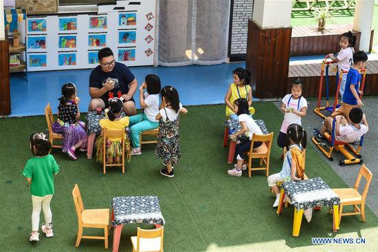 Guo Xinwang talks with children at the Xiaoxihu kindergarten in Nanjing, capital of east China's Jiangsu Province, Sept. 6, 2018. Guo, born in 1993 and graduated from the Jiangsu Normal University, became the first and only male teacher of the Xiaoxihu kindergarten three years ago. There are 400 plus male teachers in Nanjing nowadays, up to three percent of the whole teachers working in kindergartens. (Xinhua/Li Bo)