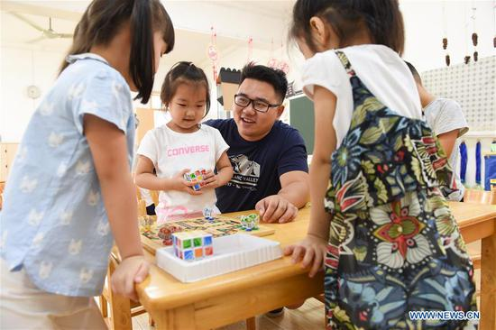 Guo Xinwang has fun with children at the Xiaoxihu kindergarten in Nanjing, capital of east China's Jiangsu Province, Sept. 6, 2018. Guo, born in 1993 and graduated from the Jiangsu Normal University, became the first and only male teacher of the Xiaoxihu kindergarten three years ago. There are 400 plus male teachers in Nanjing nowadays, up to three percent of the whole teachers working in kindergartens. (Xinhua/Li Bo)
