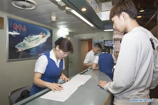 A Chinese passenger goes through boarding procedure on the ferry