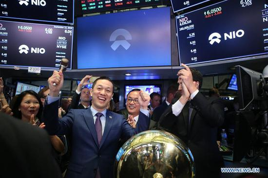 William Li (L, front), founder and chairman of Chinese electric vehicle start-up NIO Inc., celebrates after ringing a bell as NIO stock begins trading at the New York Stock Exchange in New York, the United States, on Sept. 12, 2018. NIO Inc., a Chinese electric vehicle start-up, rang the New York Stock Exchange (NYSE) opening bell on Wednesday in celebration of its initial public offering (IPO). The company, trading under the ticker symbol of NIO, announced the pricing of its IPO of 160,000,000 American depository shares (ADSs), at 6.26 U.S. dollars per ADS for a total offering size of approximately 1 billion dollars, assuming the underwriters do not exercise their option to purchase additional ADSs. Founded in 2014, NIO, dubbed as China's Tesla, is a pioneer in China's premium electric vehicle market. (Xinhua/Qin Lang)