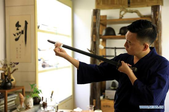 Yan Peng checks a repaired ancient weapon in Shijiazhuang, north China's Hebei Province, Sept. 11, 2018. Yan Min, dedicated to ancient weapon restoration for more than 30 years, has hitherto repaired over 500 pieces of ancient weapons with his son Yan Peng. Influenced by his father, Yan Peng quit his job and embarked on restoring ancient weapons in the year of 2015. The sophisticated craftsmanship of ancient weapon restoration embodies working procedures of polishing, burnishing, grinding etc.