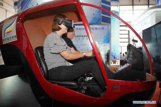 A visitor experiences helicopter simulator at the 15th China-ASEAN Expo in Nanning City, south China's Guangxi Zhuang Autonomous Region, Sept. 12, 2018. High-tech exhibits attracted many visitors at the expo. (Xinhua/Cai Yang)
