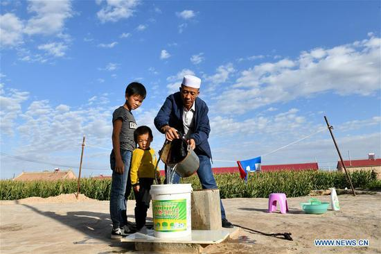 Villager He Jinwen (R) gets water from well in Hejiakouzi Village of Hanjiaoshui Township in Zhongning County, northwest China's Ningxia Hui Autonomous Region, Sept. 6, 2018. In 2004, a project diverting water from the Yellow River eased Hanjiaoshui's water shortage. Many migrant workers returned hometown. Under the guidance of local government, they planted watermelon and developed cultivation industry. In March of 2017, Ningxia started the construction of another water project to improve water supplies in Hanjiaoshui. (Xinhua/Guo Xulei)