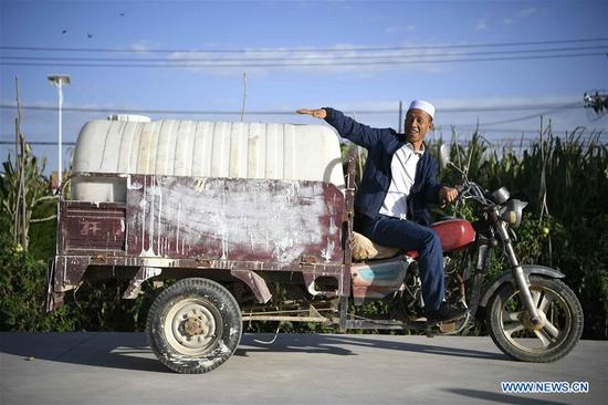 Villager He Jinwen introduces his container once being used for getting water from other places in Hejiakouzi Village of Hanjiaoshui Township in Zhongning County, northwest China's Ningxia Hui Autonomous Region, Sept. 6, 2018. In 2004, a project diverting water from the Yellow River eased Hanjiaoshui's water shortage. Many migrant workers returned hometown. Under the guidance of local government, they planted watermelon and developed cultivation industry. In March of 2017, Ningxia started the construction of another water project to improve water supplies in Hanjiaoshui. (Xinhua/Wang Peng)