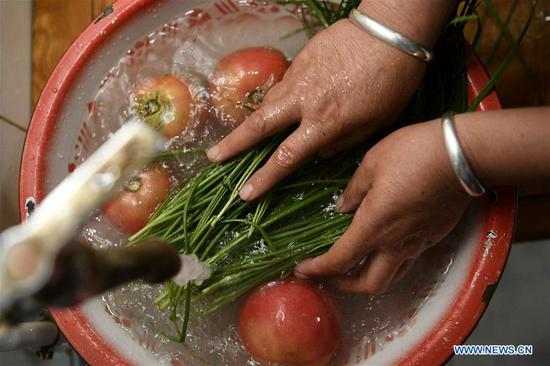 Villager Jin Fenghua washes vegetables in Hejiakouzi Village of Hanjiaoshui Township in Zhongning County, northwest China's Ningxia Hui Autonomous Region, Sept. 6, 2018. In 2004, a project diverting water from the Yellow River eased Hanjiaoshui's water shortage. Many migrant workers returned hometown. Under the guidance of local government, they planted watermelon and developed cultivation industry. In March of 2017, Ningxia started the construction of another water project to improve water supplies in Hanjiaoshui. (Xinhua/Wang Peng)