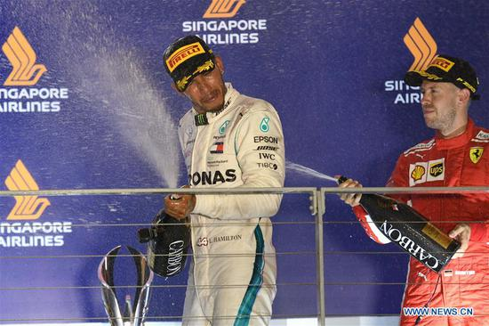 First-placed Mercedes' driver Lewis Hamilton of Britain reacts during the awarding ceremony of the 2018 Singapore Formula One Grand Prix held at the Marina Bay Street Circuit in Singapore, on Sept. 16, 2018. (Xinhua/Then Chih Wey)