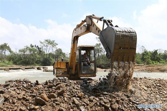 A worker drives a digger to clean riverway in Yangchun City of Yangjiang, south China's Guangdong Province, Sept. 19, 2018. After super typhoon Mangkhut ravaged Guangdong, the disaster relief work is underway. (Xinhua/Zhang Jiayang)
