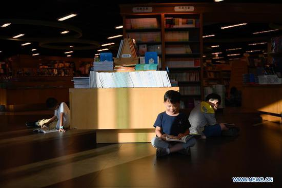 Children read books at a bookstore during the week-long National Day holiday in Hangzhou, capital of east China's Zhejiang Province, Oct. 5, 2018. (Xinhua/Huang Zongzhi)
