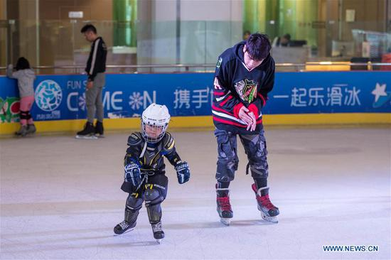 A coach instructs a child in skating at an ice rink during the week-long National Day holiday in Kunming, capital of southwest China's Yunnan Province, Oct. 5, 2018. (Xinhua/Hu Chao)