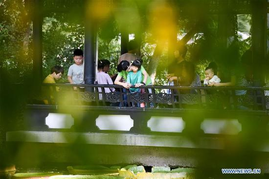 Children and their parents visit Bao Gong Garden, a scenic spot constructed in memory of Bao Zheng, a righteous government officer of ancient China's Song Dynasty (960-1279), during the week-long National Day holiday in Hefei, east China's Anhui Province, Oct. 5, 2018. (Xinhua/Zhang Duan)