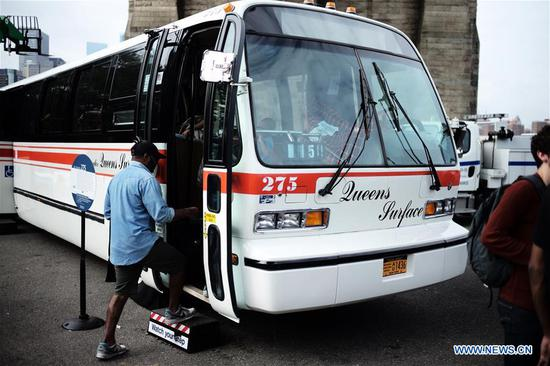 A man steps on a vintage bus during the 25th Annual Bus Festival in New York, the United States, on Oct. 7, 2018. The New York Transit Museum held its 25th annual bus festival on Sunday. The buses on display represent about 80 years of surface transit history in New York City. The oldest bus at the festival, Bus 1263, is a double-decker bus that was purchased by the Fifth Avenue Bus Company in 1930. (Xinhua/Li Muzi)
