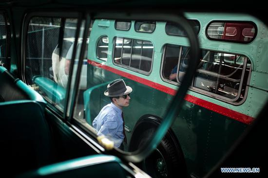 A man looks at a vintage bus during the 25th Annual Bus Festival in New York, the United States, on Oct. 7, 2018. The New York Transit Museum held its 25th annual bus festival on Sunday. The buses on display represent about 80 years of surface transit history in New York City. The oldest bus at the festival, Bus 1263, is a double-decker bus that was purchased by the Fifth Avenue Bus Company in 1930. (Xinhua/Li Muzi)