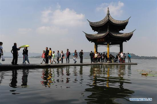 Tourists visit the West Lake scenic area in Hangzhou, capital of east China's Zhejiang Province, Oct. 7, 2018, the last day of the week-long National Day holidays. Hangzhou has received over 17 million tourists in the national day holidays. (Xinhua/Huang Zongzhi)