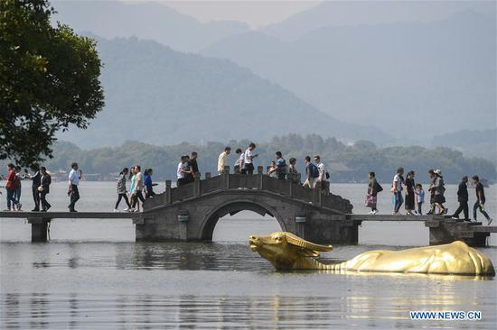 Tourists visit the West Lake scenic area in Hangzhou, capital of east China's Zhejiang Province, Oct. 7, 2018, the last day of the week-long National Day holidays. Hangzhou has received over 17 million tourists in the national day holidays.(Xinhua/Huang Zongzhi)