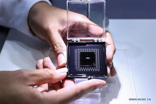 A staff member shows a photonic AI chip during a press preview of the 2018 National Mass Innovation and Entrepreneurship Week in Beijing, capital of China, Oct. 8, 2018. The weekly event will run from October 9 to 15. (Xinhua/Zhang Yuwei)