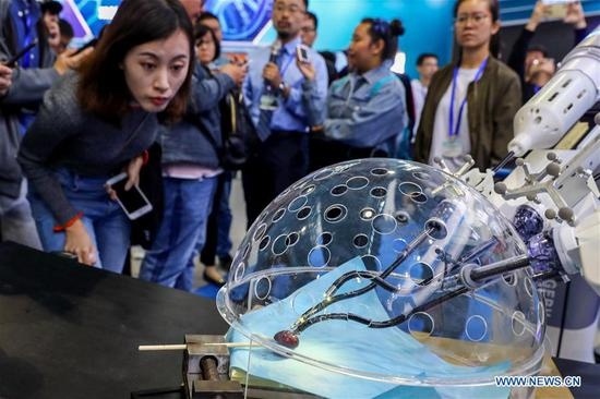 Members of the press look at a porotic laparoscopic surgery robot system during a press preview of the 2018 National Mass Innovation and Entrepreneurship Week in Beijing, capital of China, Oct. 8, 2018. The weekly event will run from October 9 to 15. (Xinhua/Zhang Yuwei)