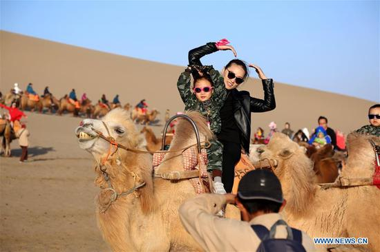 Tourists visit the Crescent Spring and Mingsha Mountain (Singing Sand Dune) scenic site in Dunhuang, northwest China's Gansu Province, Oct. 3, 2018. China witnessed 726 million domestic tourists during the National Day holidays on Oct. 1-7, growing by 9.43 percent year on year. (Xinhua/Zhang Xiaoliang)