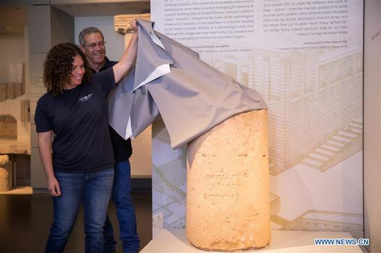 "Danit Levy(Front) of the Israel Antiquities Authority (IAA) unveils a stone column drum with the inscription of Hebrew name of Jerusalem on it at a press conference in the Israel Museum in Jerusalem, Oct. 9, 2018. A unique stone inscription dating back to first century, with the earliest known full Hebrew spelling of the word ""Jerusalem"", was presented on Tuesday. (Xinhua/JINI)"