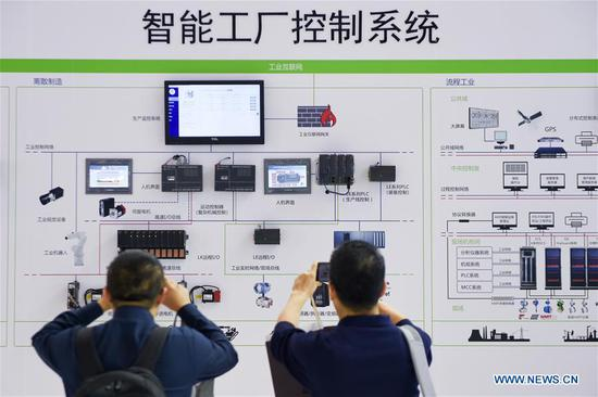 Visitors look at a smart factory control system during the World Intelligent Manufacturing Summit (WIMS) 2018 in Nanjing, east China's Jiangsu Province, Oct. 11, 2018. The WIMS 2018 opened at the Nanjing International Expo Center on Thursday. The event attracts over 1,900 exhibitors worldwide to showcase the latest technologies, advanced products, development trends and cutting-edge solutions in the intelligent manufacturing field. (Xinhua/Li Bo)