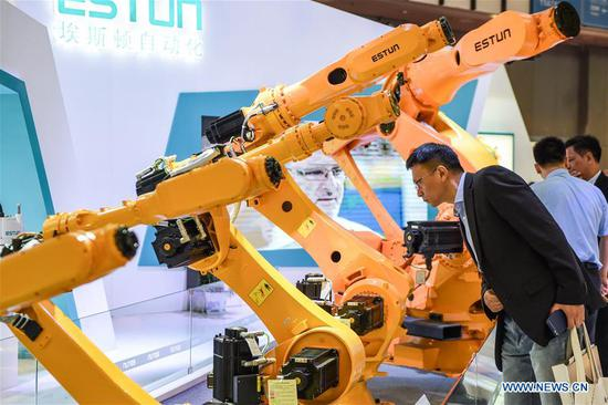 A visitor looks at an automatic robot during the World Intelligent Manufacturing Summit (WIMS) 2018 in Nanjing, east China's Jiangsu Province, Oct. 11, 2018. The WIMS 2018 opened at the Nanjing International Expo Center on Thursday. The event attracts over 1,900 exhibitors worldwide to showcase the latest technologies, advanced products, development trends and cutting-edge solutions in the intelligent manufacturing field. (Xinhua/Li Bo)