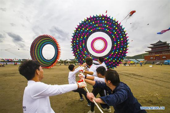 Competitors fly a big kite at a kite flying contest held at Lulanqingsha scenic spot in Daishan County of Zhoushan, east China's Zhejiang Province, Oct. 14, 2018. (Xinhua/Yao Feng)