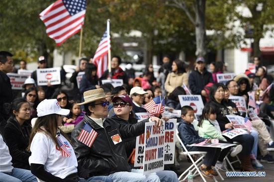 """People demonstrate at the Copley Square in Boston, the United States, on Oct. 14, 2018. Hundreds of Asian Americans on Sunday afternoon held demonstrations in central Boston to show support for a lawsuit accusing Harvard University of discriminating against Asian American applicants by using """"de facto racial quotas, racial stereotypes and higher standards."""" Harvard has denied the charges. The lawsuit, launched by the Students for Fair Admissions (SFFA), an anti-Affirmative Action advocacy group, will go to trial on Monday at a U.S. District Court in Boston. (Xinhua/Liu Jie)"""