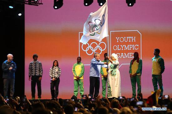 International Olympic Committee President Thomas Bach (5th L) hands over the Olympic flag to Soham El Wardini (3rd R), mayor of Dakar, during the closing ceremony of the 2018 Summer Youth Olympic Games at the Youth Olympic Village in Buenos Aires, Argentina, on Oct. 18, 2018. (Xinhua/Li Ming)