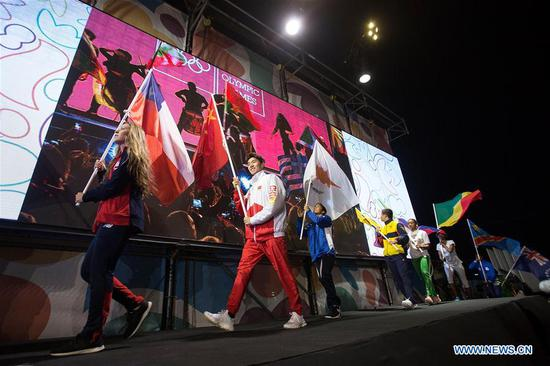 The flag bearers walk on the stage during the closing ceremony of the 2018 Summer Youth Olympic Games at the Youth Olympic Village in Buenos Aires, Argentina, on Oct. 18, 2018. (Xinhua/Martin Zabala)