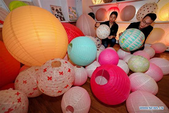 Staff workers view paper lanterns at a factory in Jian'ou City, southeast China's Fujian Province, Nov. 4, 2018. Paper lanterns produced by local enterprises and workshops are now exported to markets in Europe, North America and Southeast Asia. (Xinhua/Zhang Guojun)