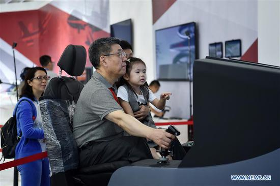 Citizens experience a flying simulator at the exhibition area of the upcoming China International Aviation and Aerospace Exhibition in Zhuhai, south China's Guangdong Province, Nov. 5, 2018. The exhibition is scheduled to be held on Nov. 6-11. (Xinhua/Liang Xu)