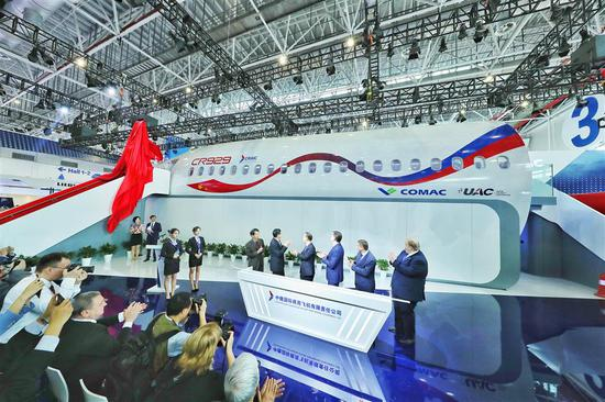 Officials with the Commercial Aircraft Corporation of China and United Aircraft Corp of Russia unveil the prototype for display of the CR929 wide-body jet at the Airshow China in Zhuhai.