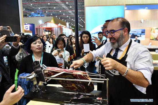 A Spanish ham exhibitor shows Iberian ham to visitors at the first China International Import Expo (CIIE) in Shanghai, east China, Nov. 6, 2018. More than 3,000 companies from over 130 countries and regions attended the CIIE. (Xinhua/Li Xin)
