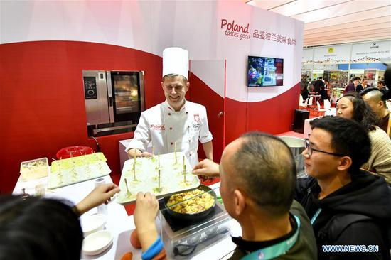 A staff member from Poland provides traditional food at the first China International Import Expo (CIIE) in Shanghai, east China, Nov. 6, 2018. More than 3,000 companies from over 130 countries and regions attended the CIIE. (Xinhua/Li Xin)